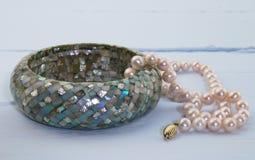 Le bleu a peint le fond avec le collier rose de perle et le bleu mozaic Photographie stock