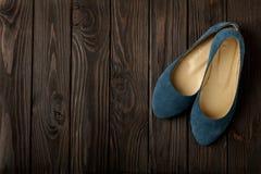 Le ` bleu s de femmes chausse des ballerines sur le fond en bois Images stock