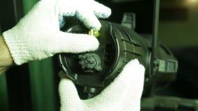 Le bloc d'éclairage dans les gants enlève la couverture avec une lampe d'halogène du projecto de profil banque de vidéos