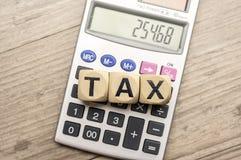 Le bloc en bois de lettre assemblent l'impôt et la calculatrice de mot Photos stock