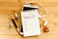 Le bloc-notes avec le crayon et le téléphone intelligent pour fixer les BUTS 2018 Image stock