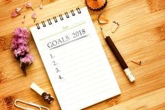 Le bloc-notes avec le crayon sur la table en bois pour fixer les BUTS 2018 Photographie stock