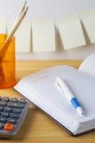 Le bloc-notes avec le récipient de stylo avec des crayons, calculatrice sont sur une table en bois Sur le mur près de la table a  photo stock