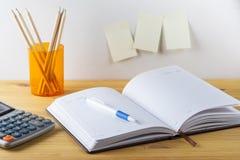Le bloc-notes avec le récipient de stylo avec des crayons, calculatrice sont sur une table en bois Sur le mur près de la table a  photos stock