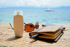 Le bloc-notes fermé, lunettes de soleil téléphonent avec des écouteurs et le tube blanc de solaire crème se protègent sur la tabl Images libres de droits