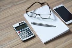 Le bloc-notes, la calculatrice, le smartphone, les verres et le ruban ballpen image stock