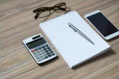 Le bloc-notes, la calculatrice, le smartphone, les verres et le ruban ballpen photo libre de droits