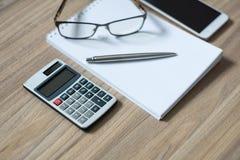 Le bloc-notes, la calculatrice, le smartphone, les verres et le ruban ballpen images libres de droits