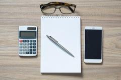 Le bloc-notes, la calculatrice, le smartphone, les verres et le ruban ballpen photographie stock