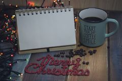 Le bloc-notes, la tasse bleue et l'inscription marient Noël Image stock