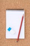 Le bloc-notes, le crayon et la gomme à effacer spiralés sur le liège apprêtent Photos stock