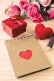 Le bloc-notes vide avec le boîte-cadeau rouge et le coeur rouge forment Image stock