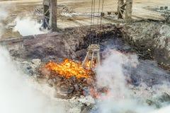 Le bloc supérieur mécanique de multivalve attaquent pour le transport des morceaux d'un rouge ardent de fer de la fonte sur une é photographie stock libre de droits