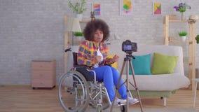 Le blogger africain de femme a désactivé dans un fauteuil roulant avec une coiffure Afro avant la caméra banque de vidéos