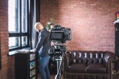 Le blogger d'homme dispose à s'enregistrer sur le blog visuel sur l'appareil-photo dans le studio photos stock