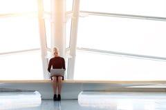 Le blogger de femme s'assied dans l'espace de Co-travail à l'arrière-plan de bâtiment de gratte-ciel avec l'espace de copie Photo stock