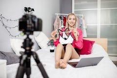 Le blogger de jeune fille habillé dans des vêtements à la mode lumineux est filmé pour ses expositions de vidéo de blog se repose image stock