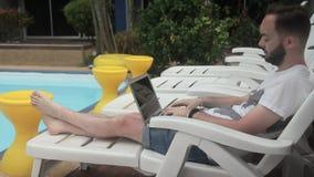 Le blogger de voyage de jeunes écrit un courrier sur l'ordinateur portable près de la piscine dans l'hôtel banque de vidéos
