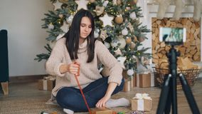 Le blogger habile de femme enseigne ses disciples à décorer des cadeaux de Noël se reposant sur le plancher tenant la boîte actue banque de vidéos
