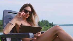 Le blogger sexy de fille dans un maillot de bain écrit des messages par la tablette au sujet de la vie à la campagne chic dans le banque de vidéos