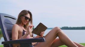 Le blogger sexy de fille dans un maillot de bain écrit des messages par la tablette au sujet de la vie à la campagne chic dans le clips vidéos
