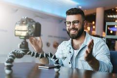 Le blogger visuel masculin barbu crée le contenu visuel pour son canal Le vlogger d'homme se soulage sur la caméra avec le trépie image stock