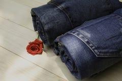 Le blue jeans hanno piegato con la rosa rossa sulla tavola di legno e sulle sedere di legno Fotografie Stock
