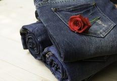 Le blue jeans hanno piegato con la rosa rossa sulla tavola di legno e sulle sedere di legno Immagini Stock