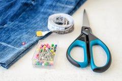 Le blue jeans mettono, rotolo del nastro del sarto con i centimetri ed i pollici, multi colorato hanno diretto i perni di cucito  fotografia stock