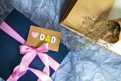 Le boîte-cadeau bleu-foncé avec la décoration de ruban et le papa roses d'amour Photographie stock