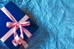 Le boîte-cadeau bleu-foncé avec la décoration rose de ruban sur le bleu de polka Images stock