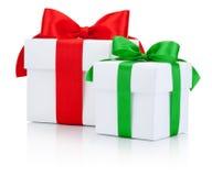 Le boîte-cadeau de deux blancs a attaché le ruban vert et rouge d'isolement sur le fond blanc Image libre de droits