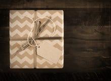 Le boîte-cadeau de fête avec des rayures de chevron dans la sépia modifie la tonalité Photographie stock