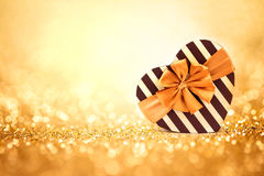 Le boîte-cadeau de formes de coeur de rouge sur le backgrou léger abstrait de scintillement Images stock
