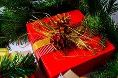 Le boîte-cadeau de Noël avec les cônes d'or de pin et le sapin s'embranchent Image libre de droits