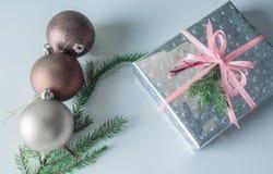 Le boîte-cadeau de Noël enveloppé en papier de scintillement avec Noël joue sur un fond blanc Non isolé Photographie stock