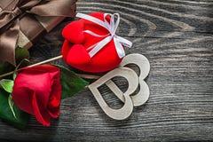Le boîte-cadeau emballé par coeurs de rose de rouge sur des célébrations de conseil en bois escroquent Photos stock