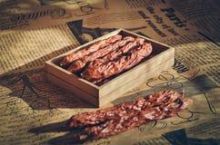 Le boîte-cadeau en bois a fumé des saucisses épicées Saucisses de chasse Fond et foyer mous chauds photos libres de droits