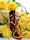 Le boîte-cadeau entrebâillé avec les fleurs jaunes est les roses entourées sur un fond blanc Images libres de droits