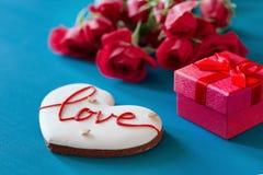 Le boîte-cadeau et le bouquet des roses et du pain d'épice sous forme de coeur avec l'inscription aiment pour des vacances sur en Photo stock