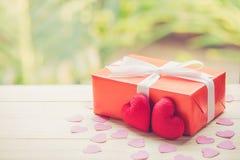 Le boîte-cadeau et le coeur rouges forment sur le dessus de table en bois avec le fond de bokeh de tache floue de vert de nature Photo libre de droits