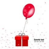 Le boîte-cadeau et le ballon rouges avec des confettis dirigent la carte de voeux Images stock