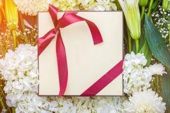 Le boîte-cadeau et les fleurs encadrent le backbround sur un backgrou en bois de plancher Image stock
