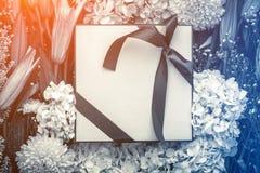Le boîte-cadeau et les fleurs encadrent le backbround sur un backgrou en bois de plancher Photographie stock