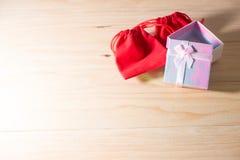 Le boîte-cadeau et le sac rouge de cadeau ont enveloppé des présents de Noël et de Newyear avec des arcs et des rubans, fond de l Image libre de droits
