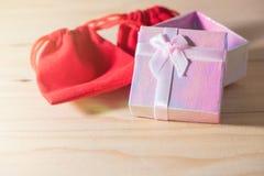 Le boîte-cadeau et le sac rouge de cadeau ont enveloppé des présents de Noël et de Newyear avec des arcs et des rubans, fond de l Photographie stock libre de droits