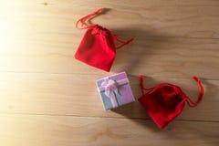 Le boîte-cadeau et le sac rouge de cadeau ont enveloppé des présents de Noël et de Newyear avec des arcs et des rubans, fond de l Image stock