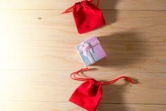 Le boîte-cadeau et le sac rouge de cadeau ont enveloppé des présents de Noël et de Newyear avec des arcs et des rubans, fond de l Images stock
