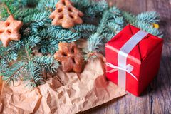 Le boîte-cadeau, les biscuits et le pin s'embranchent sur un fond de table Cadre actuel de rouge Concept de Noël Image libre de droits
