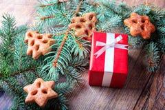 Le boîte-cadeau, les biscuits et le pin s'embranchent sur un fond de table Cadre actuel de rouge Concept de Noël Images libres de droits
